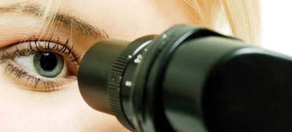 Enteris BioPharma close-up of female scientist looking into microscope.
